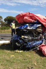 A wrecked car in which four people died near Lara (left) after a collision with another vehicle being driven the wrong way on the freeway by a driver who also died.