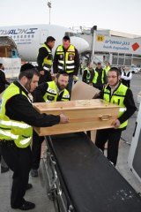 Volunteers  unload a coffin carrying a victim of the Toulouse shooting in France for burial in Israel.
