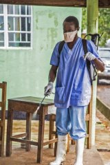 A health worker sprays disinfectant against the deadly Ebola virus at the Kenema Government Hospital in Sierra Leone on Saturday.
