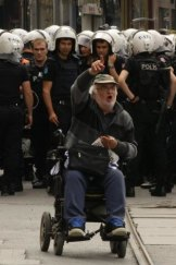 """""""Spray me if you have to"""": A wheelchair-bound protester confronts the police."""