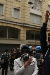 A masked policeman raises his arms in Istanbul's fashionable Istiklal Avenue during the anniversary protests.
