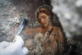 An archaeologist works to uncover the newly discovered fresco.