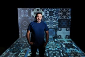 Artist Khaled Sabsabi in front of giant mosaic video work Syria.