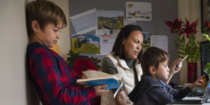 Dee Mills helping her sons,Jaxon,9,and Harrison,5,with their school work in their Matraville home.