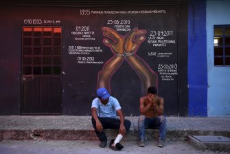 Luís (left) and friend Fidel at La 72 in Mexico, where a mural commemorates massacres of migrants by drug cartels.