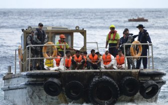 Australian Customs officials and navy personnel escort asylum seekers to Christmas Island in 2013.