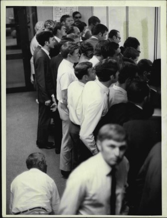 An investor is down on his hands and knees, peering between legs to get a look at the boards on the Perth Stock Exchange. This was the scene in the public gallery at Exchange House morning's call. October 23, 1969, at the height of the Poseidon nickel boom.
