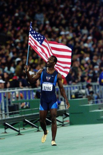 American Michael Johnson celebrates his victory in the men's 400m.