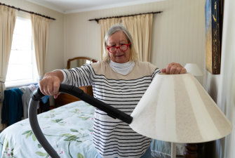 Margot White vacuums coal dust from a bedside lamp that she says has collected there for the past month.