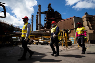 BlueScope employees (from left) Chris Page, Michael Reay, and Craig Nealon walk past part of the blast furnace operating at Port Kembla.