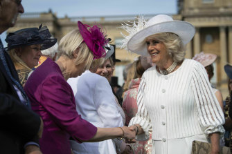 Camilla the Duchess of Cornwall greets guests during a pre-pandemic garden party at Buckingham Palace.