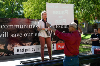 A protester holds a 'Pause the Plan' sign in front of Sussan Ley at a rally in Albury.