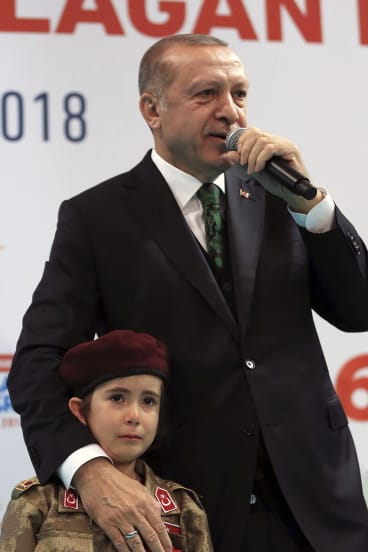 Turkish President Recep Tayyip Erdogan stands with a young girl in military uniform as he speaks to his ruling party members, in Kahramanmaras, Turkey.