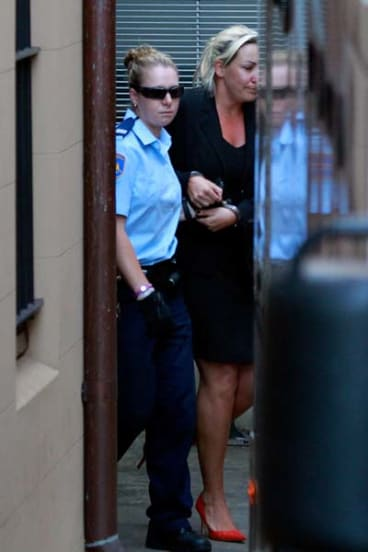 Keli Lane being lead away by a security officer from the Supreme Court.
