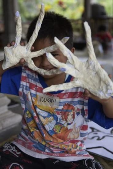 A child from a remote Indonesian community creates puppets during a visit by members of Melbourne's Polyglot Theatre.