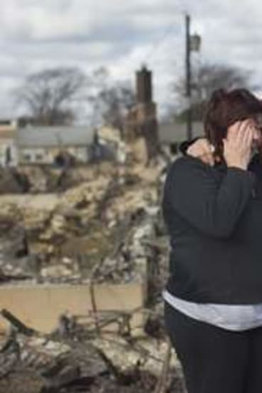 Neighbors  embrace after looking through the wreckage of their homes post-Hurricane Sandy.