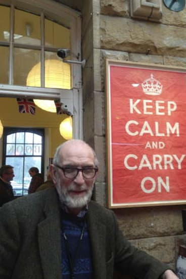 Stuart Manley with the poster he found at the bottom of a box of books and began selling in his second-hand bookshop.