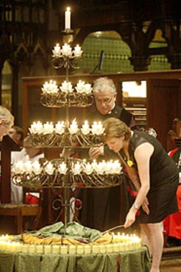 Carol Matthews lights a candle.