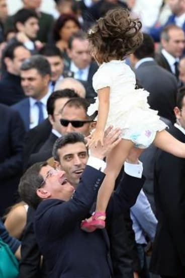 Turkish Prime Minister Ahmet Davutoglu celebrates the liberation of his country's consular staff with the daughter of freed Turkish consul Ozturk Yilmaz as Mr Yilmaz looks on.