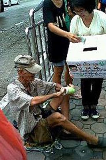 A homeless Thai man donates to flood victims in this photo posted on Facebook.