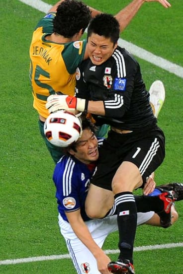 Japan's goalkeeper Eiji Kawashima and defender Daiki Iwamasa (bottom) challenge Australia's midfielder Mile Jedinak.