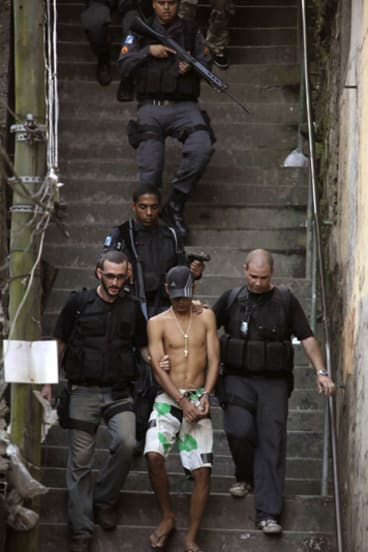 A suspected gang member is arrested in the Morro Santo Amaro slum in Rio de Janeiro.