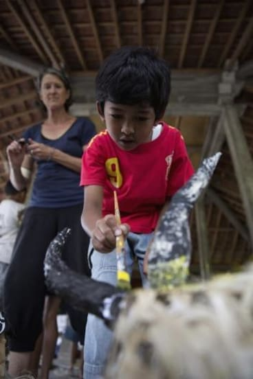A child from a remote Indonesian community paints puppets during a visit by members of Melbourne's Polyglot Theatre.