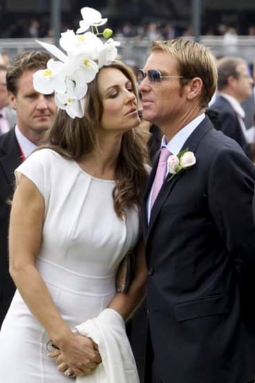 Kiss and sell … Liz Hurley and Shane Warne at the races.