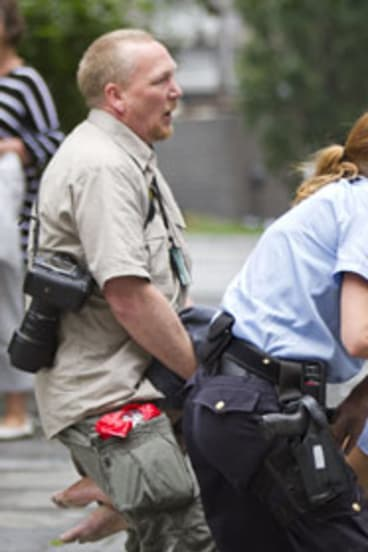 Police carry a wounded woman from the blast scene in central Oslo.
