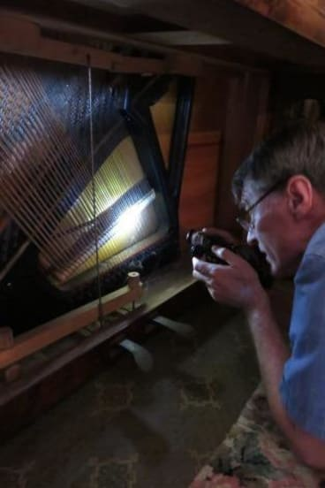 Chris Leslie makes a preliminary assessment of a now-restored piano.