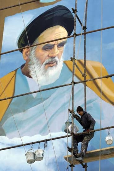 Keeping watch … a painter works on an election mural of the Iranian revolutionary leader, Ayatollah Khomeini, in Tehran.