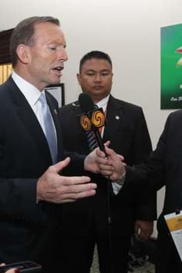 Prime Minister Tony Abbott speaks with an Australian-based journalist who was not allowed to his press conference during the East Asia Summit in Brunei.