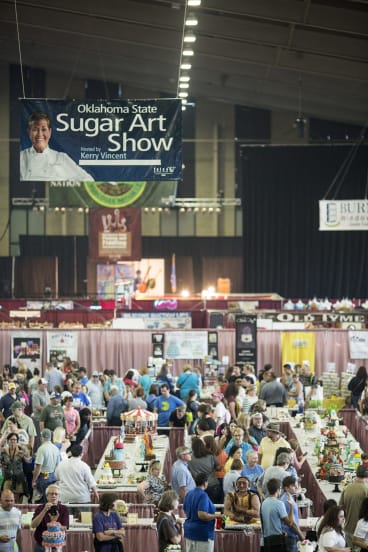 "Show time: Crowds admire the ""sugar art"" at Tulsa, including hamburger cakes and cakes that look like dinosaur sjulls."