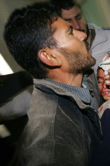 A wounded Palestinian boy is carried into a Gaza City hospital.