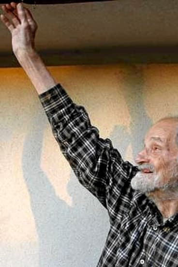 Lloyd Shapley raises his arm after being notified of winning the 2012 economics Noble prize.