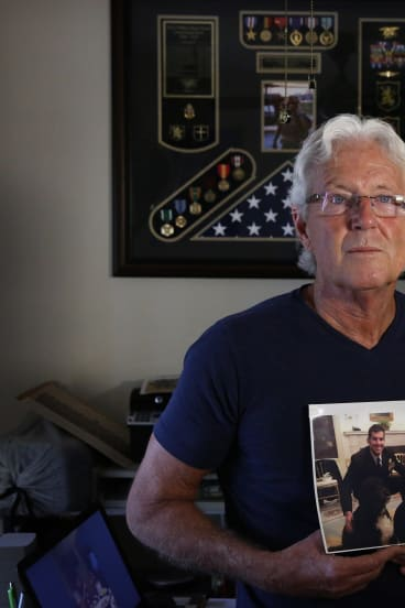 """William Owens holds a photo of his son Navy SEAL William """"Ryan"""" Owens in Lauderdale by the Sea, Florida."""