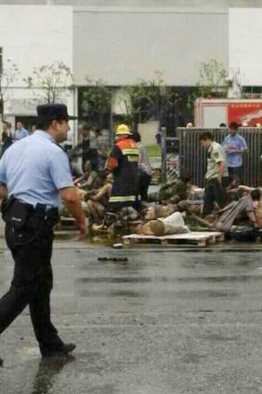 Emergency workers and injured people in front of the factory in Kunshan, China.