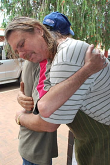 A friend consoles fruit shop owner Tom Carter (right), who lost his home and orchard in the Toodyay fires.
