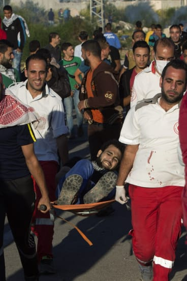 Palestinian protesters evacuate a man who was injured during clashes with Israeli soldiers securing the entrance of the Erez border crossing on Friday.