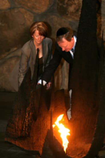 Julia Gillard and Peter Costello rekindle the eternal flame at Jerusalem's Yad Vashem Holocaust museum. Picture: Gali Tibbon.
