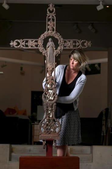 Slice of history: Gallery manager Ruth Lovell with the former grave-site cross, which is to be auctioned.