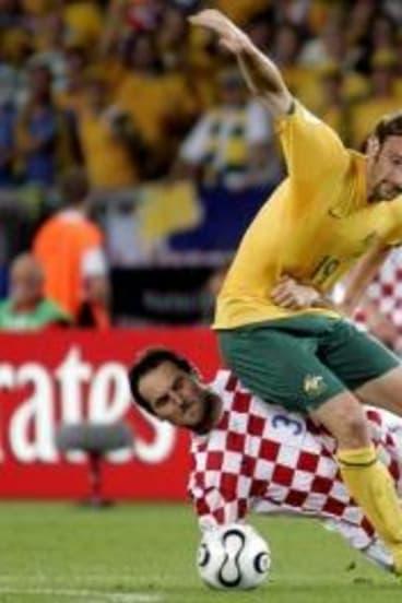 Josip Simunic tackles Josh Kennedy.