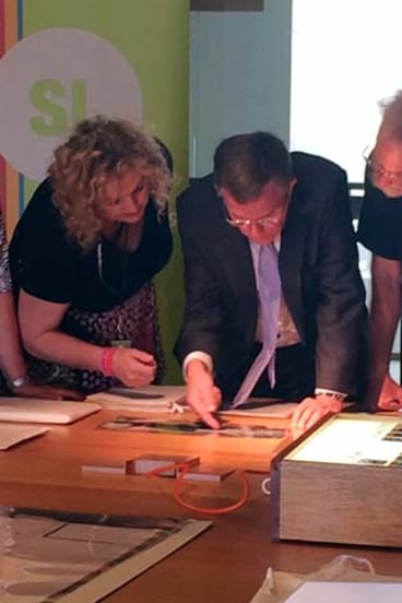 Artist Jon Barlow Hudson (right), Arts Minister Ian Walker and State Librarian Janette Wright look at the documents.