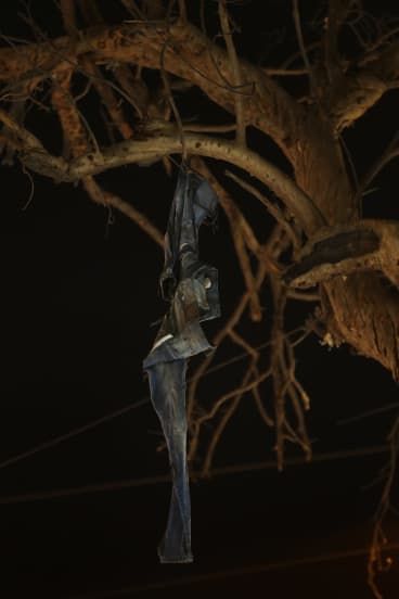 The jeans of a bombing victim hang from a burnt tree in the Karrada district of Baghdad.