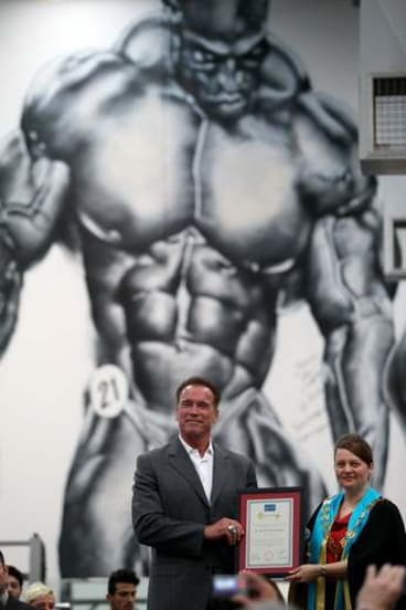 Arnold Schwarzenegger receives the keys to the city of Melton from Mayor Kathy Majdlik beneath a mural of bodybuilder Ronnie Coleman.