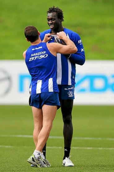 Brent Harvey (L) has a playful shove with Majak Daw at a Kangaroos training session.
