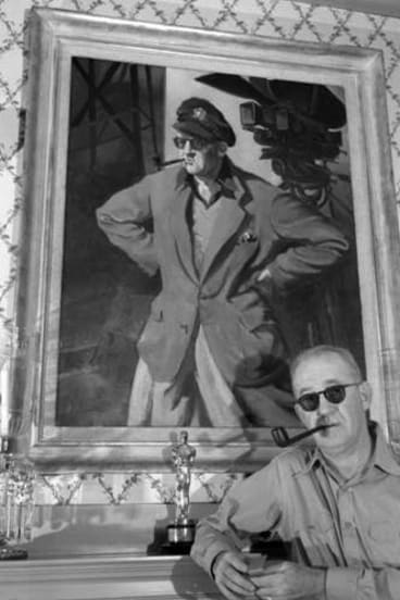 Man and myth: Ford poses in front of a portrait of himself.