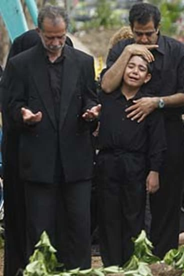 Eight-year-old Iranian Sinan, brought to Rookwood cemetery to bury his father, is comforted.