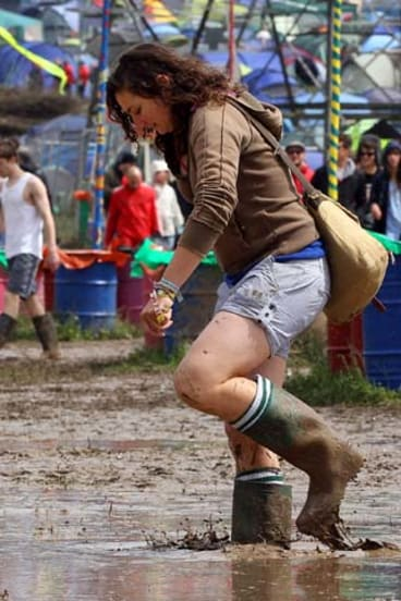 A gum-booted festival goer sloshes through the Glastonbury mud.