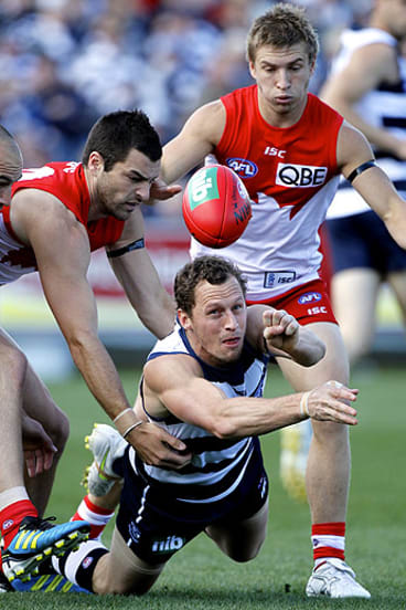 Cat attack: Geelong midfielder James Kelly shoots out a handball.